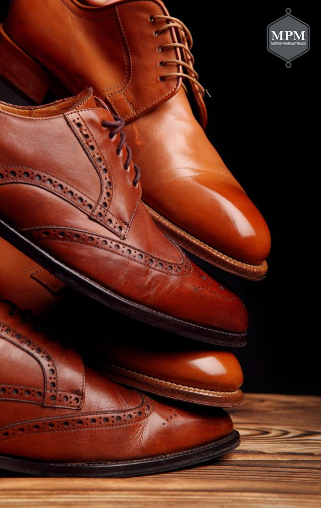 Four toes one on one of brown shoes brogues and derby on the wooden table.Shoes shine concept of luxury shoes